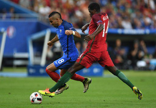 France's forward Dimitri Payet (L) is challenged by Portugal's midfielder William Carvalho during the Euro 2016 final football match between Portugal and France at the Stade de France in Saint-Denis, north of Paris, on July 10, 2016. / AFP PHOTO / PATRIK STOLLARZ